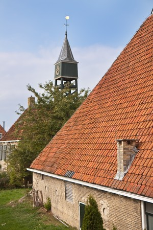 Old dutch historic farmhouse with churchtower behind it Stock Photo - 6981607