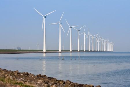 Dutch windmills along the coastline, mirroring in the calm sea photo