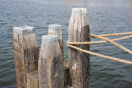 Big wooden bollard with rope of tied ship Stockfoto