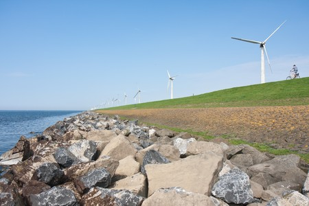 Endless dike with windmills with lonely bicycle in the Netherlands photo