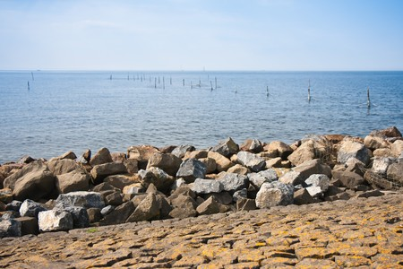 Breakwater of big rocks at Dutch coast photo