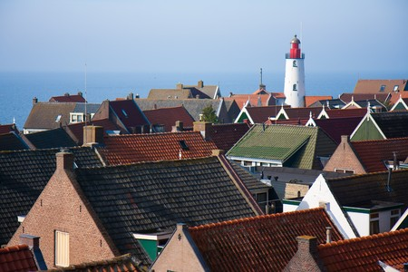 traverse: View at the lighthouse and roofs of a pittoresk old fishing village in the netherlands