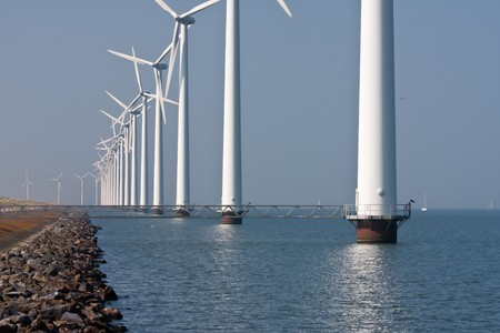 Long row of windmills standing in Dutch sea