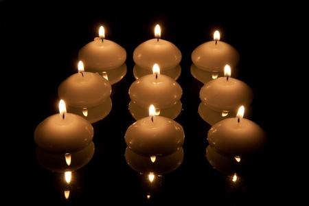 mirroring: Nine mirroring candles in the dark Stock Photo
