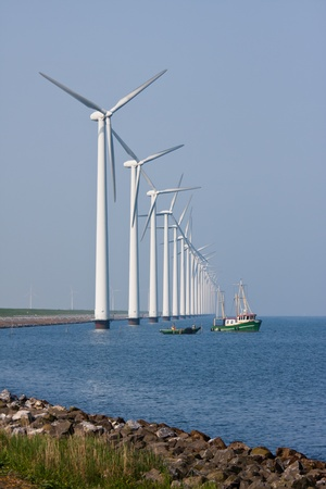 Big windturbines in the Netherlands with fishing ship photo