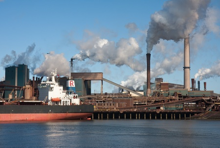 Steel factory with smokestacks and a big cargo ship in front of it photo