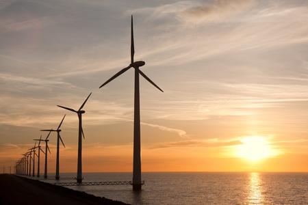 windmills: Fila de windturbines en el mar y una hermosa puesta de sol