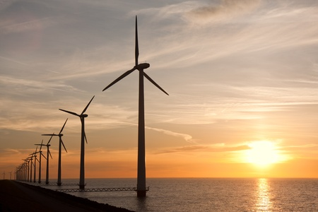Row of windturbines in the sea and a beautiful sunset