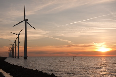 Beautiful sunset behind a long row of windturbines in the sea