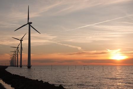 Prachtige zonsondergang achter een lange rij van windturbines in de zee Stockfoto