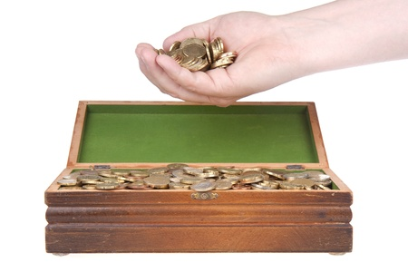 Hand full of coins over a treasure chest photo