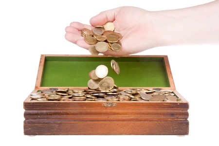 an ounce: Hand dropping coins in a treasure chest Stock Photo