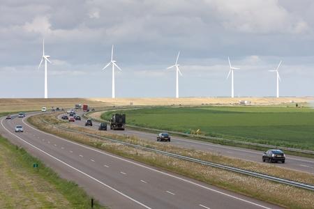 Snelweg met een lijn van grote windturbines achter het Stockfoto - 9659592