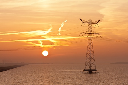 Sunrise over the Dutch sea with the silhouette of an electricty pylon photo