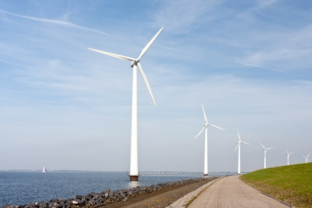 Wind turbines standing along the dyke in the Dutch sea photo