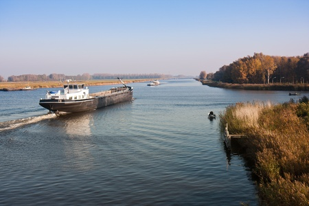 shipper: Big Dutch straight canal with fishing men and a cargo vessel