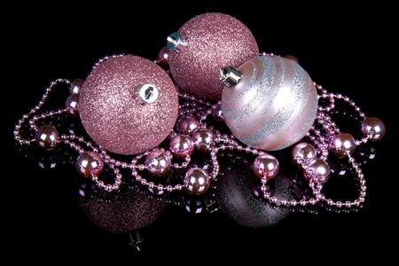 Purple Christmas balls with a string of small balls, isolated on black Stock Photo