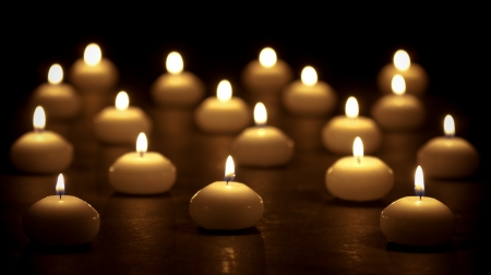 Group of burning candles at a black background with selective focus
