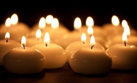 kerzen: Gruppe von brennenden Kerzen auf einem schwarzen Hintergrund mit selektiven Fokus