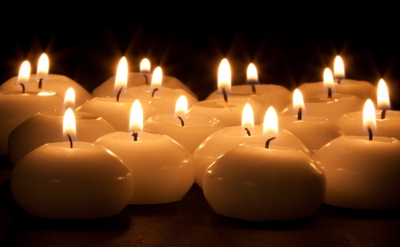 Group of burning candles at a black background photo