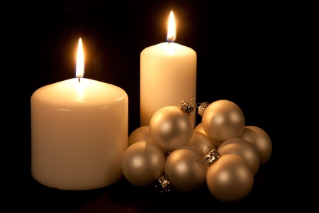 Two white candles with Christmas balls photo