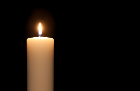 White candle isolated against a black background photo