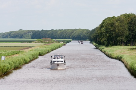 Dutch canal with pleasure yachts  through green meadows photo