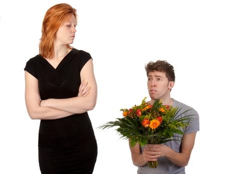 novios enojados: Muchacho joven que ofrece un ramo de flores a su novia enojada Foto de archivo