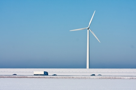 Snowy landscape with a big windturbine and a highway in front of it photo
