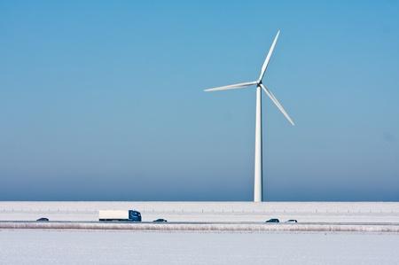 Snowy landschap met een grote windturbine en een snelweg in de voorkant van het Stockfoto - 12164382