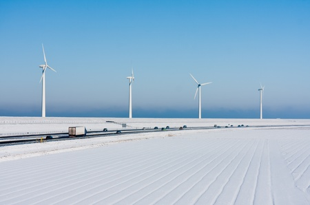 Dutch rural winter landscape with a highway and big windturbines photo