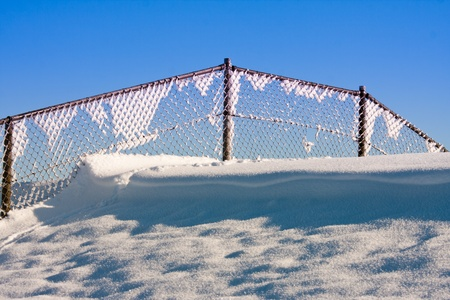 Fence covered with hoar frost against a blue sky photo