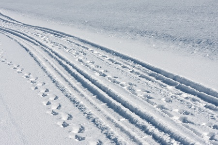 Tire tracks and footsteps in white snow photo
