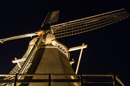 Night view of traditional Dutch wooden illuminated corn-mill photo