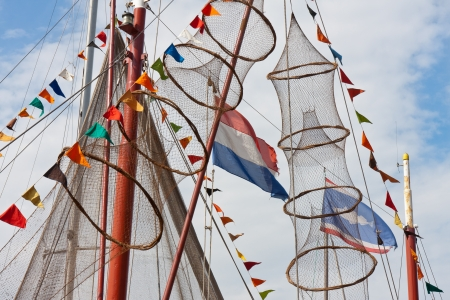 fishing ship decorated with nets and flags from holland and fishing village urk