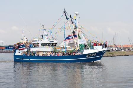 pesquero: Urk, LOS PA�SES BAJOS - 19 de mayo: Un barco de pesca decorado est� dejando el puerto durante un festival nacional de pesca Editorial