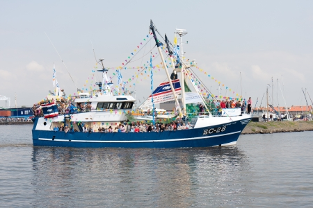 URK, THE NETHERLANDS - MAY 19: A decorated fishing ship is leaving the harbor during a National fisheries festival