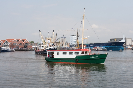fisheries: URK, THE NETHERLANDS - MAY 19: Decorated fishing ships are leaving the harbor during a National fisheries festival