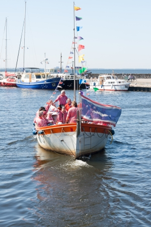 URK, THE NETHERLANDS - MAY 19: A tourist vessel with the members of a traditional sailors choir singing a shanty song at a holiday of Urk