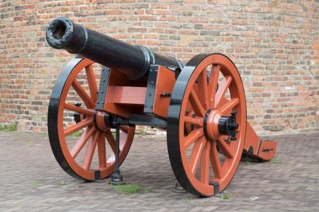 artillery: Old medieval artillery canon before a brick wall