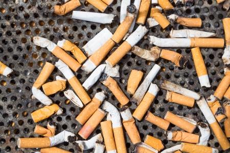 Cigarettes in a big iron ashtray photo