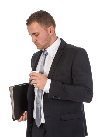 Busy businessman is having a coffeebreak; isolated on wihte photo
