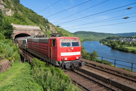 Train leaving a tunnel near the river Moselle in Germany photo