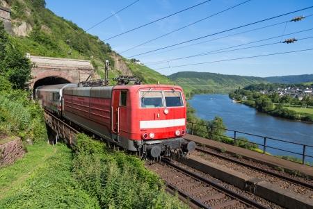 tunnel di luce: Treno che parte un tunnel nei pressi del fiume Mosella in Germania Archivio Fotografico