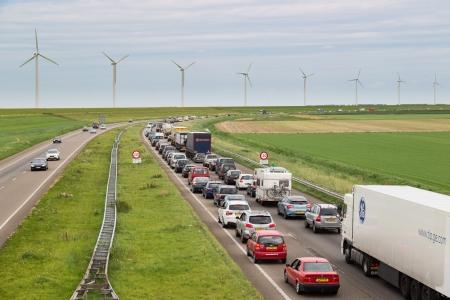 LELYSTAD - 17 augustus: Verkeer beweegt langzaam langs een drukke snelweg langs een dijk en windturbines op 17 augustus 2012 in Lelystad, Nederland Stockfoto - 17393180