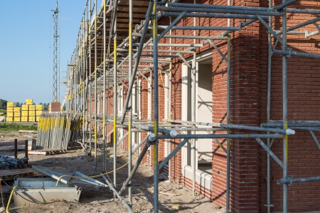 scaffold: Construction site with family houses in scaffolding