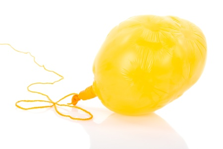 Deflated yellow balloon at a rope; isolated over white