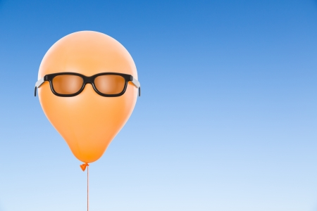 Orange Balloon with sunglasses against a blue sky with copyspace photo