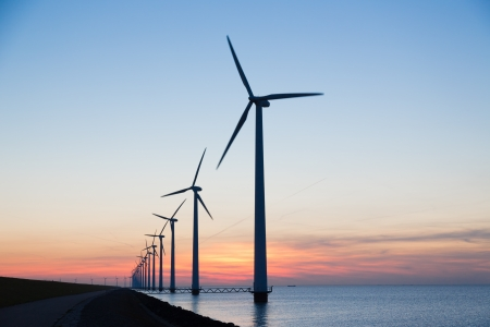 Long row of windturbines with sunset over the sea photo