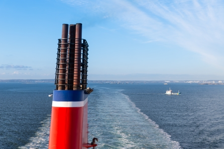 Chimney at a ship sailing a a blue sea photo